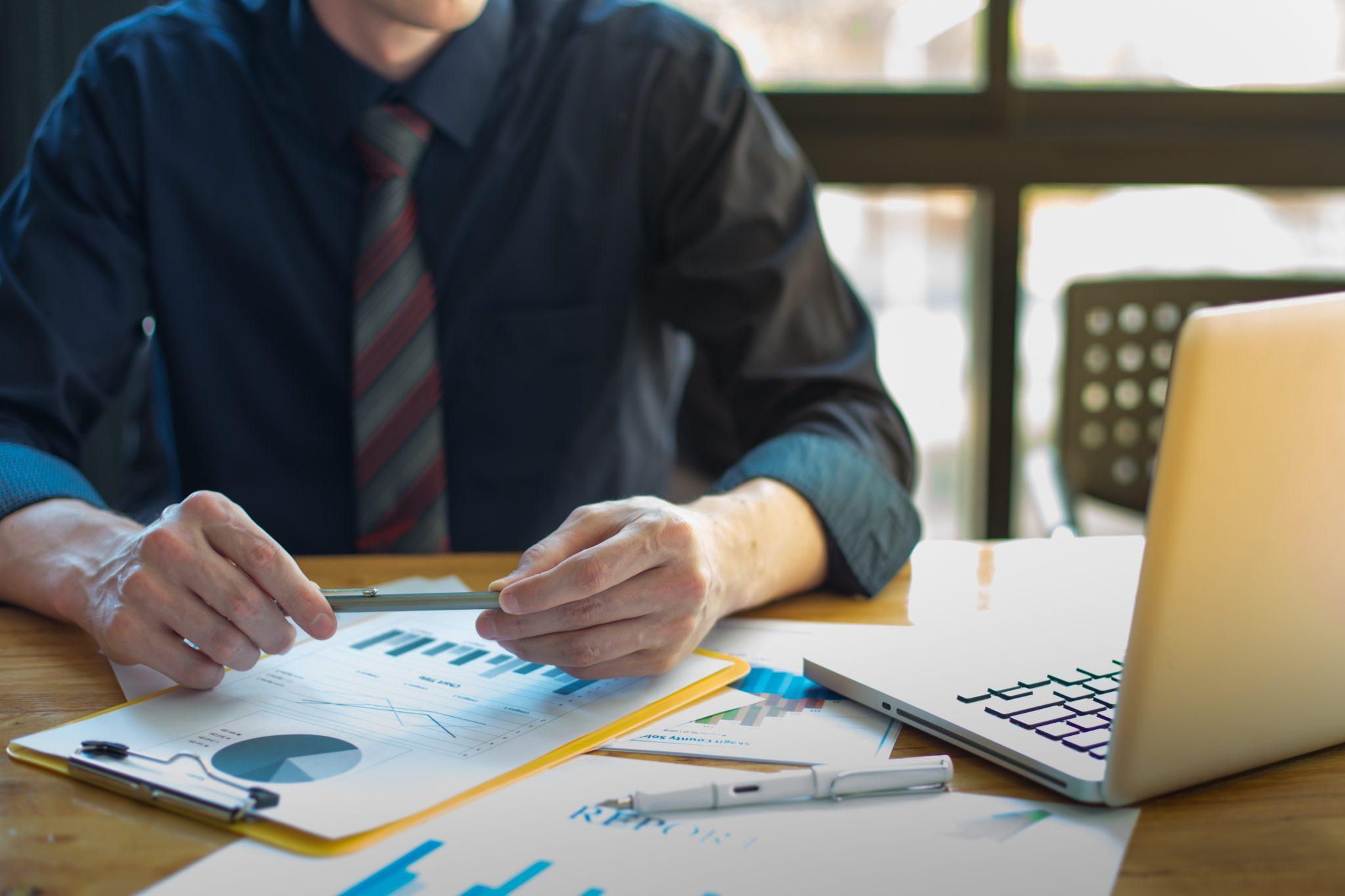Empreendedor no escritório em meio a papéis e planilhas.